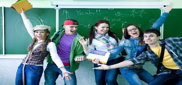 group of young students having fun on the background of the school board